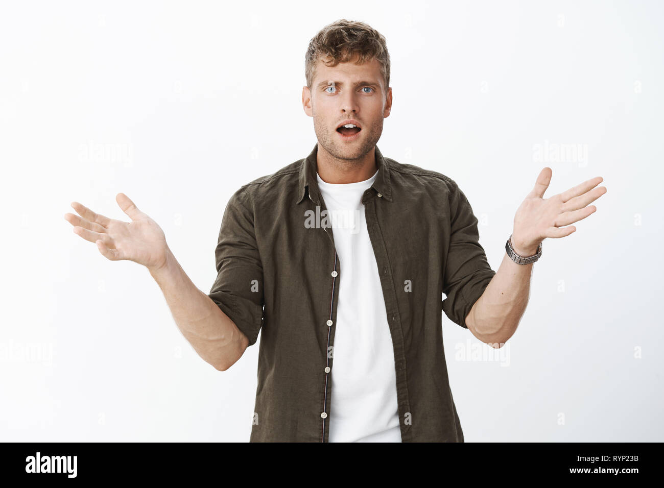 Confused handsome blond man with blue eyes raising hands sideways in dismay and clueless gesture being dumped unexpectedly standing questioned and - Stock Image