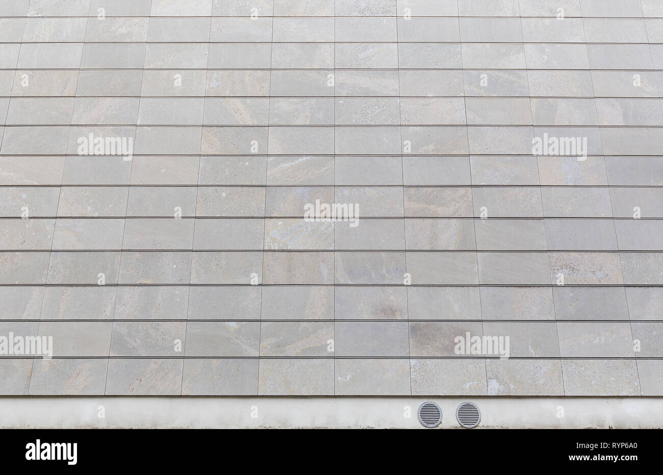 Full frame background of a new, modern and clean stone wall or building exterior. Stock Photo