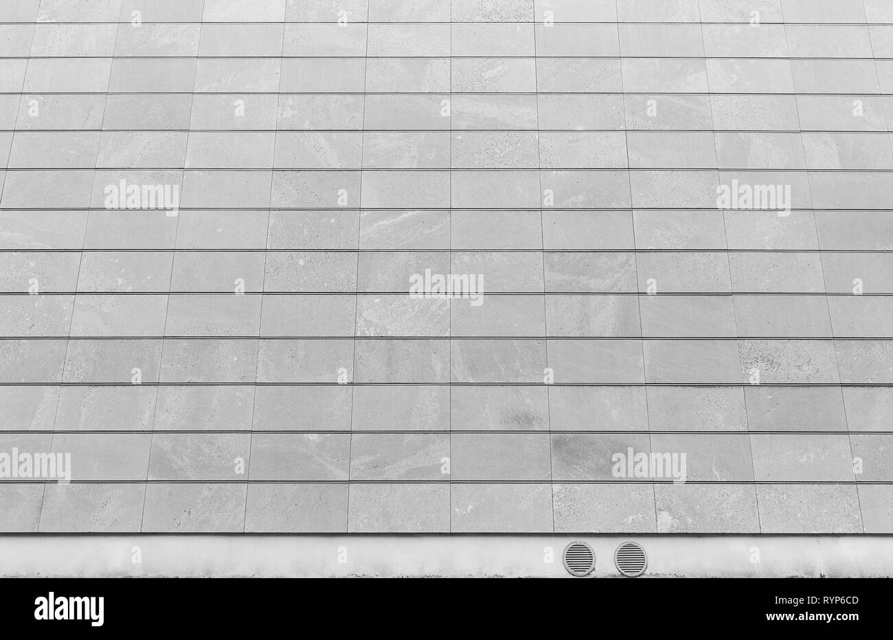 Full frame background of a new, modern and clean stone wall or building exterior in black and white. Stock Photo