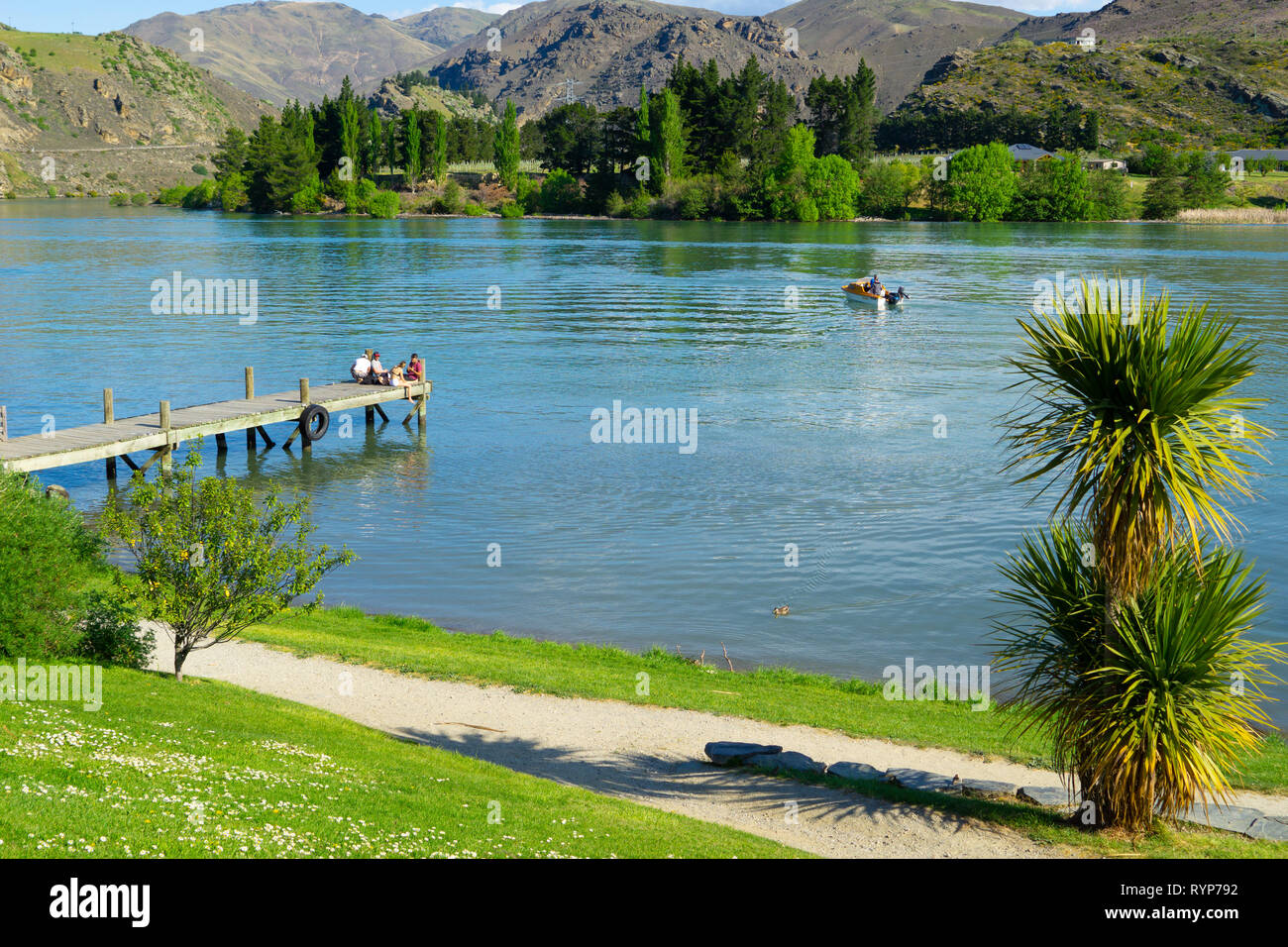 CROMWELL NEW ZEALAND - OCTOBER 21 2019; Lake Dunstan scene with young group young people sitting together on end of jetty with boat in water Cromwell  Stock Photo