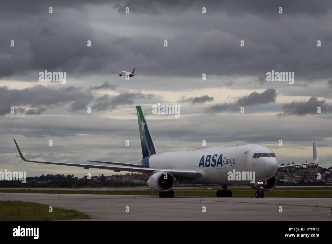 Boeing 767-300F from ABSA Cargo Airlines taxiing in Guarulhos Airport while another plane takes off. - Stock Image