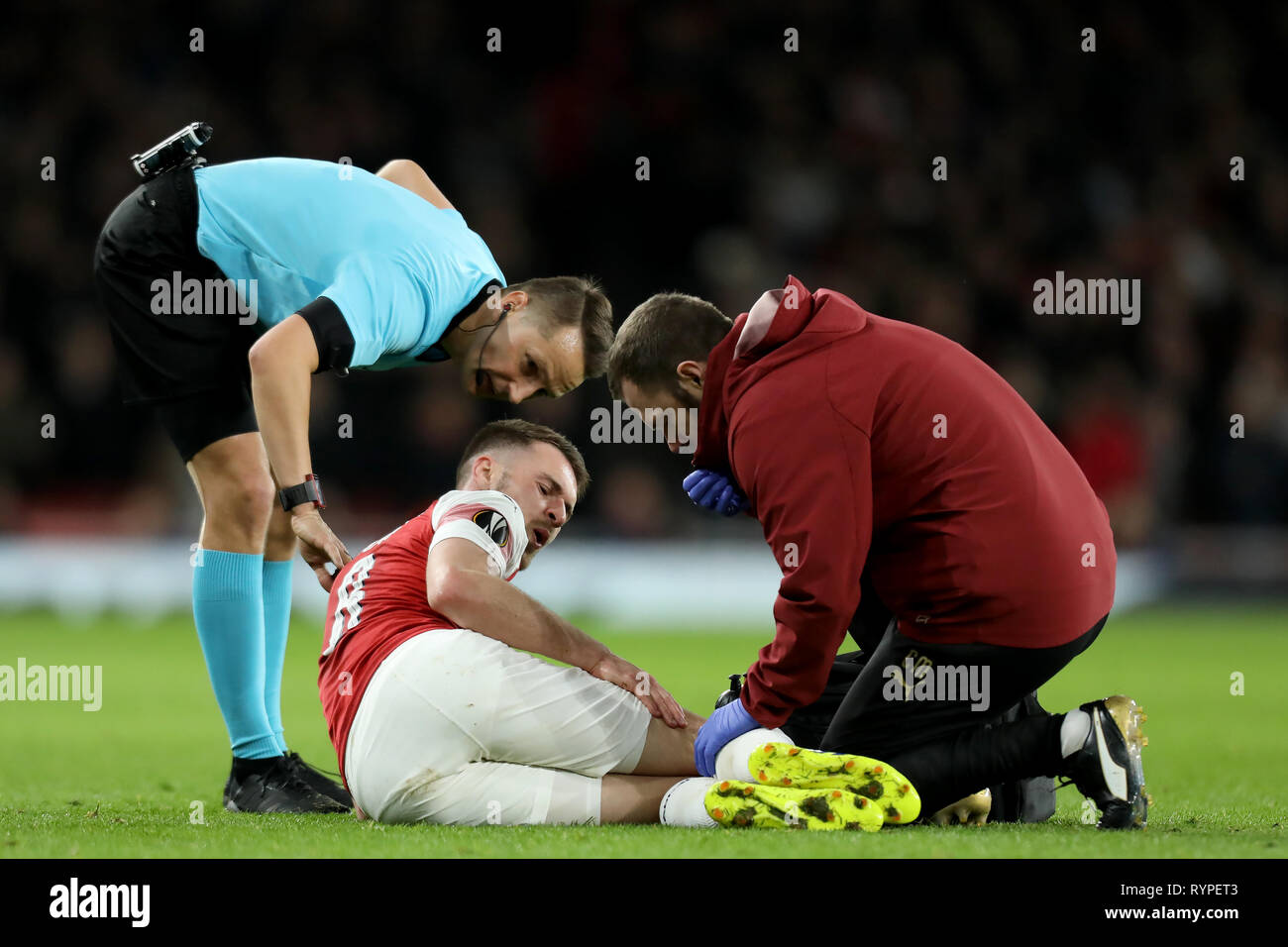 Emirates Stadium, London, UK. 14th Mar, 2019. UEFA Europa League football, round of 16, second leg, Arsenal versus Rennes; Aaron Ramsey of Arsenal goes down injured and receives treatment Credit: Action Plus Sports/Alamy Live News - Stock Image