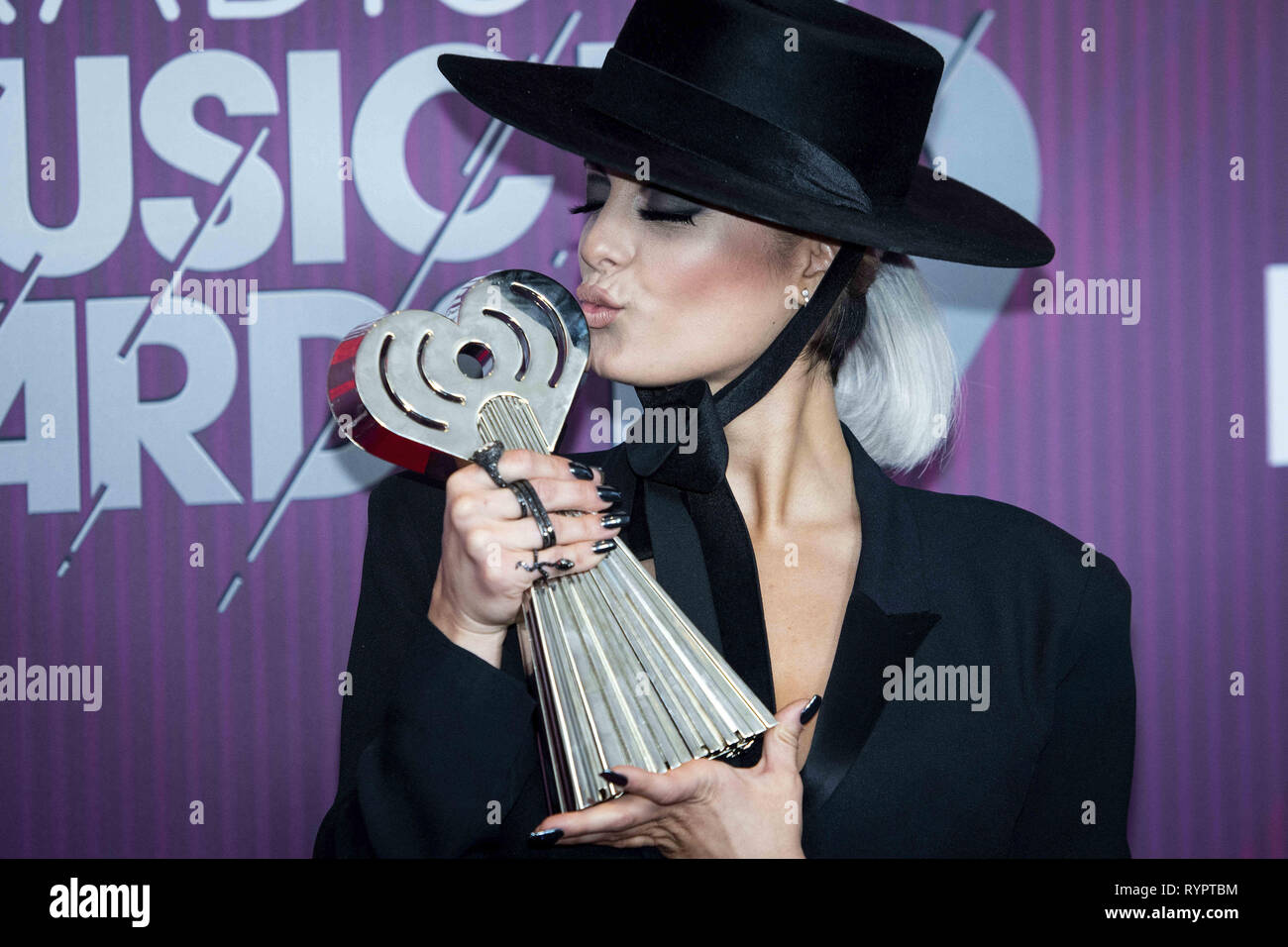 Los Angeles, California, USA. 14th Mar, 2019. BEBE REXHA, co-winner of Country Song of the Year for 'Meant to Be' kisses her award. Credit: Erick Madrid/ZUMA Wire/Alamy Live News - Stock Image