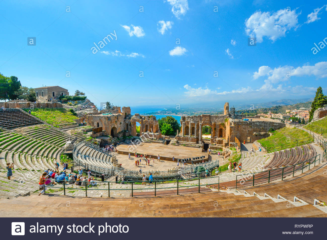 Tourists enjoy a summer afternoon at the ancient Greek Theatre on the Sicily at the resort city of Taormina, Italy. Stock Photo