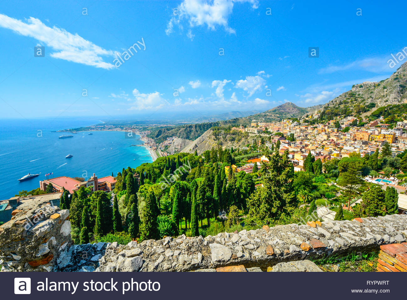 Looking down from the ancient Greek Theatre at Taormina, Italy, on the Italian island of Sicily, with boats and resorts dotting the Mediterranean sea Stock Photo
