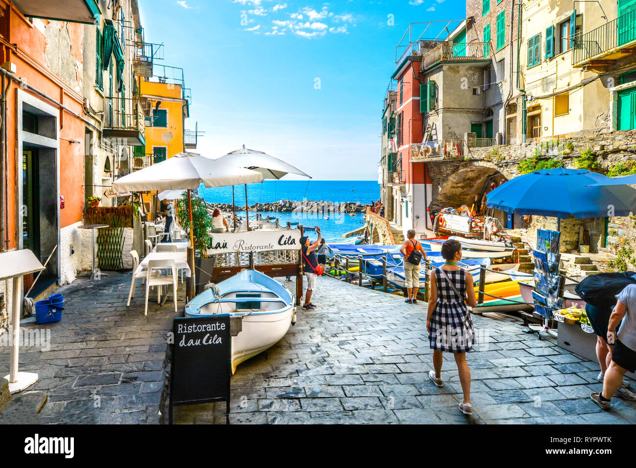 Tourists enjoy a sunny day on the Ligurian coast with the sea, cafe and boats in Riomaggiore Italy, on the Cinque Terre of the Italian Riviera Stock Photo