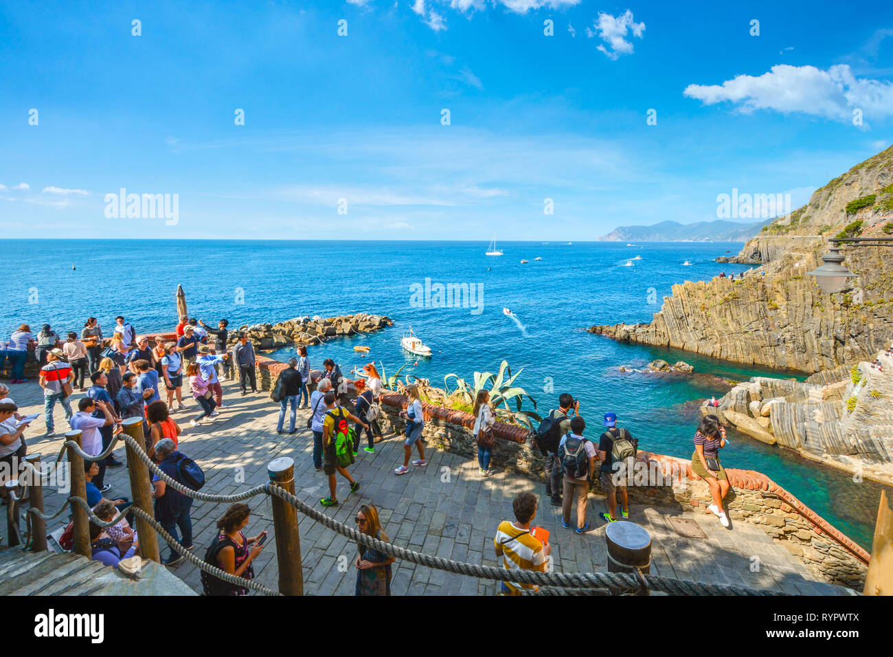 Tourists gather at the lookout point at the Cinque Terre village of Riomaggiore, Italy, with the Ligurian sea, harbor and boats behind them Stock Photo