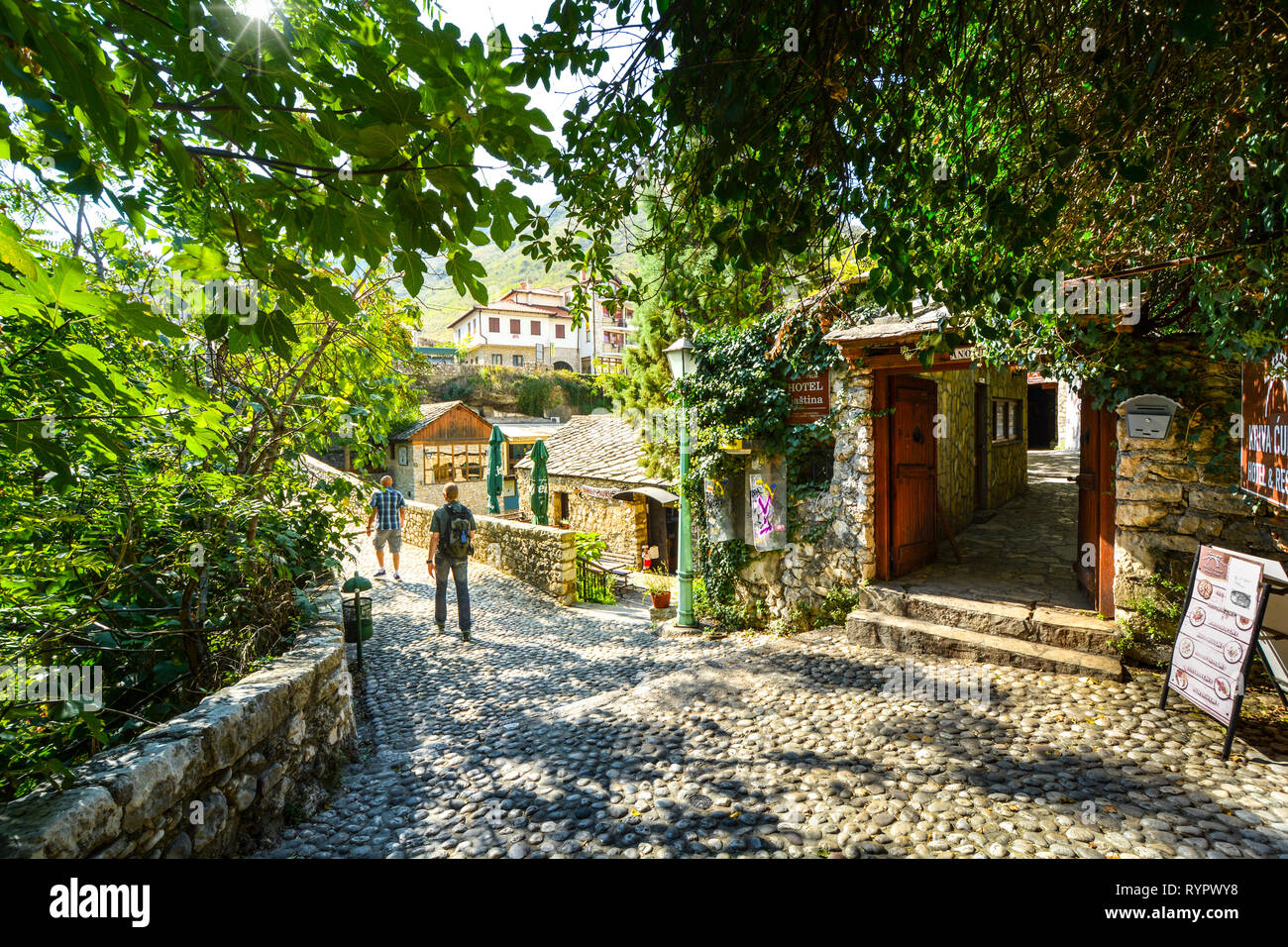 Tourists walk a cobblestone path over a bridge in the medieval city of Mostar, Bosnia on an autumn morning. Stock Photo
