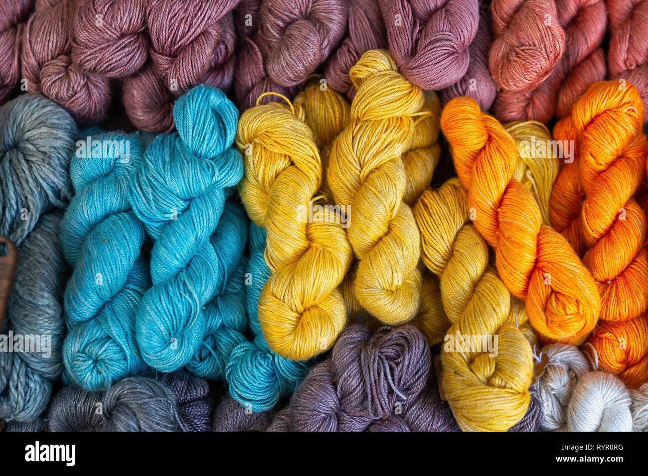 A Pile Of Natural Knitting Yarn Of Yellow Orange Blue And Brown