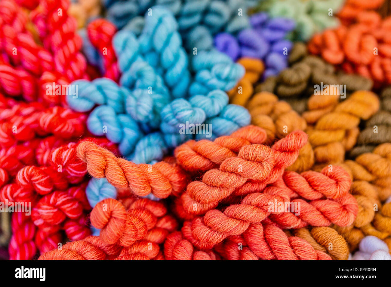 A Pile Of Natural Knitting Yarn Of Red Blue And Brown Colors Is