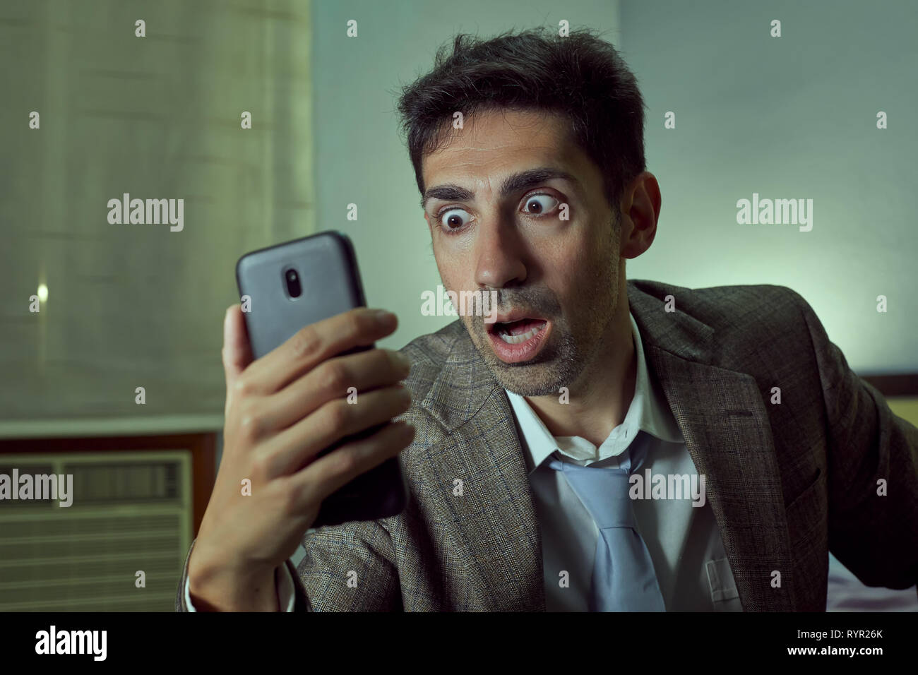 Very surprised man with tie and jacket looks at his cell. - Stock Image
