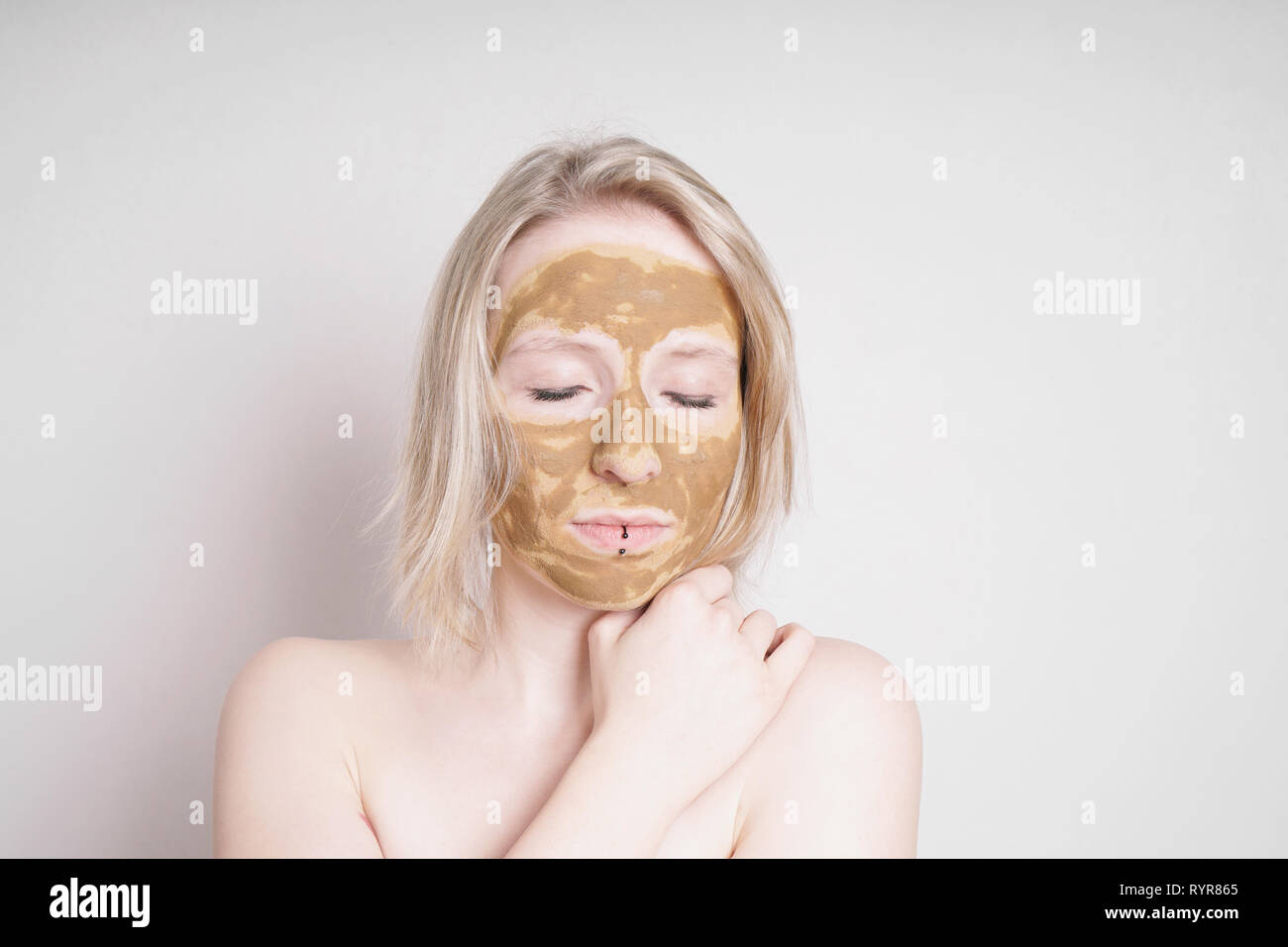 young woman with healing earth or clay beauty facial mask enjoying wellness treatment - a natural ayurveda treatment for acne or oily skin - Stock Image