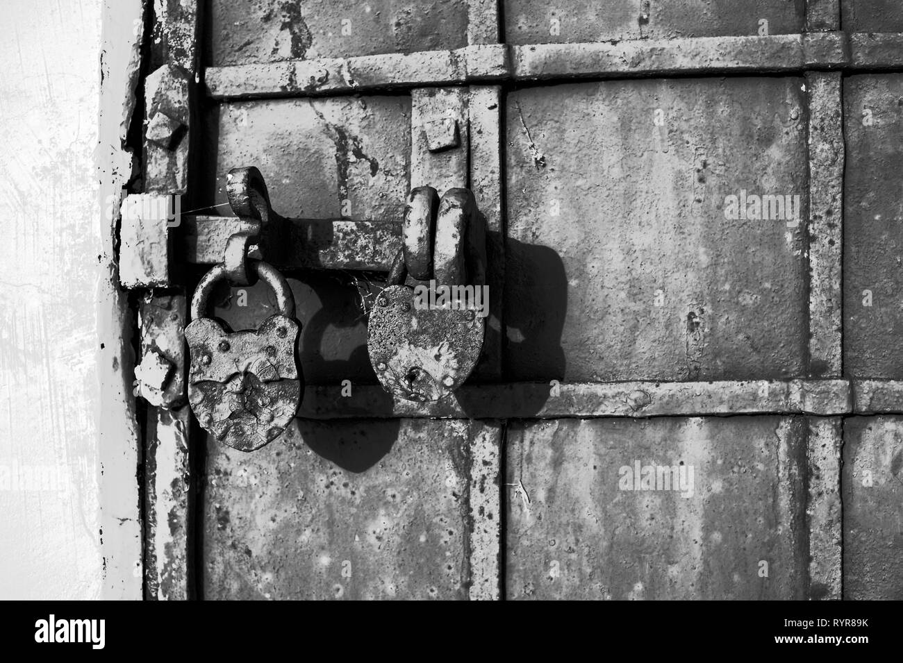 Part of a chained gate with a gate valve and two locks of an old historic building. Black and white background, retro, vintage. - Stock Image