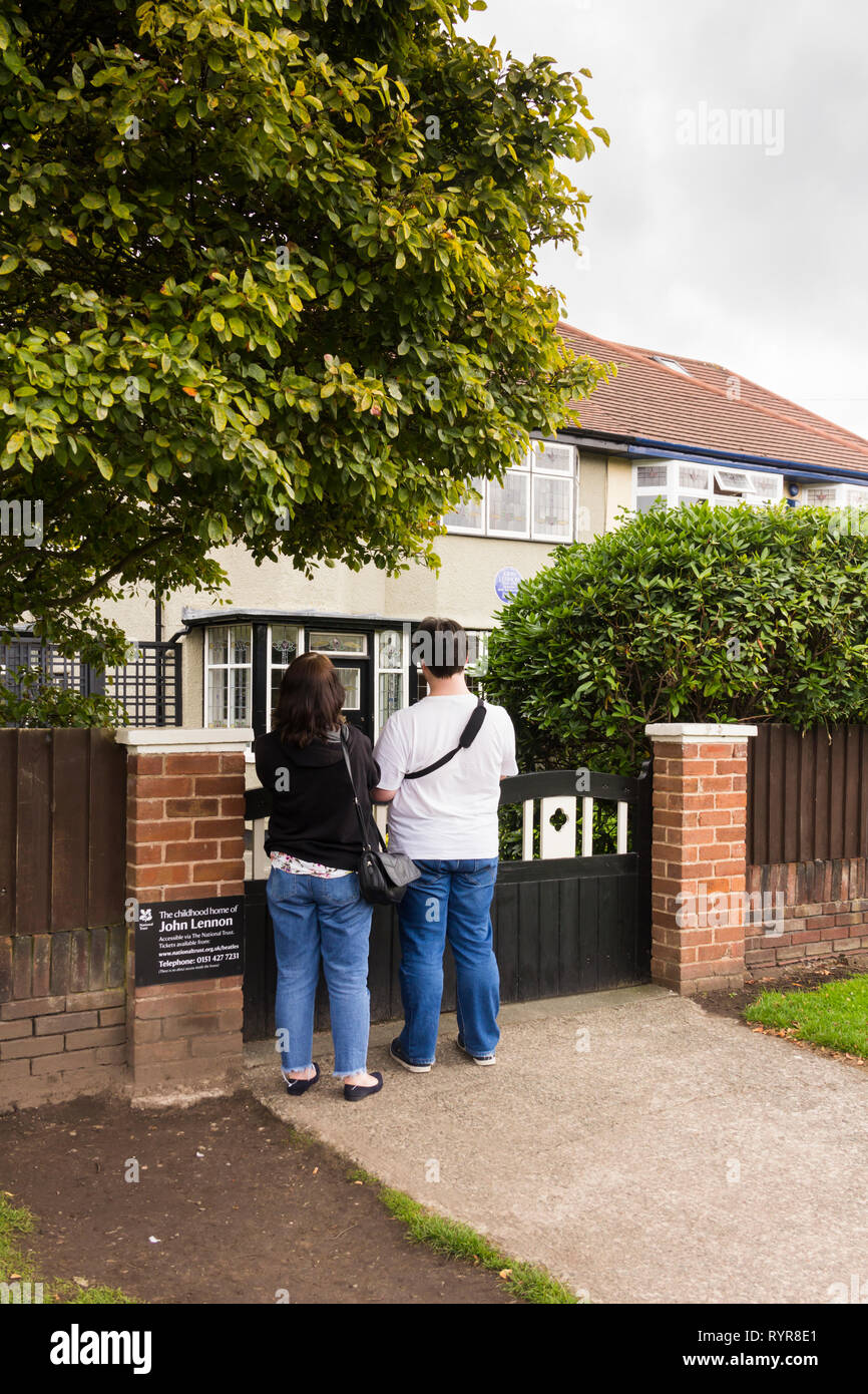 Two visitors standing at the gate to the childhood home of John Lennon, Menlove Avenue, Woolton, Liverpool. The museum to the former singer/songwriter Stock Photo