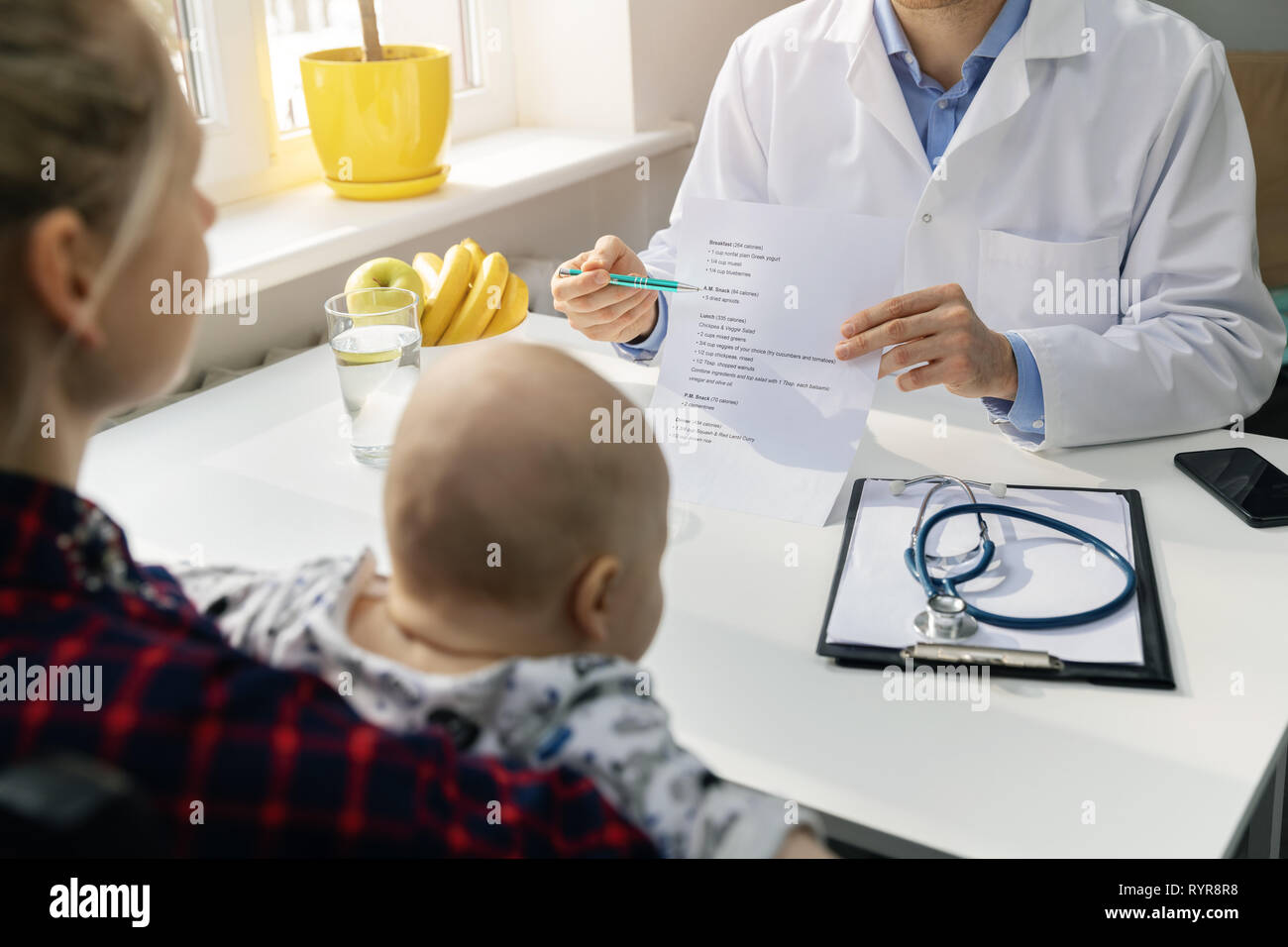 nutritionist and young mother with baby discussing healthy balanced nutrition plan in office Stock Photo
