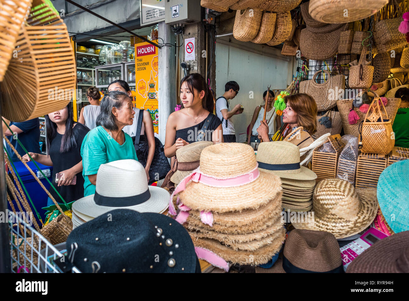 Bangkok, Thailand - May 13, 2018: three women talk to each other behind a shop counter filled with hats and wicker bags at Chatuchak Weekend Market. Stock Photo