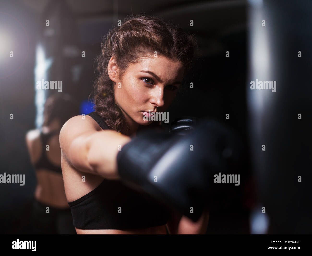 Young fighter boxer girl in training with heavy punching bag - Stock Image