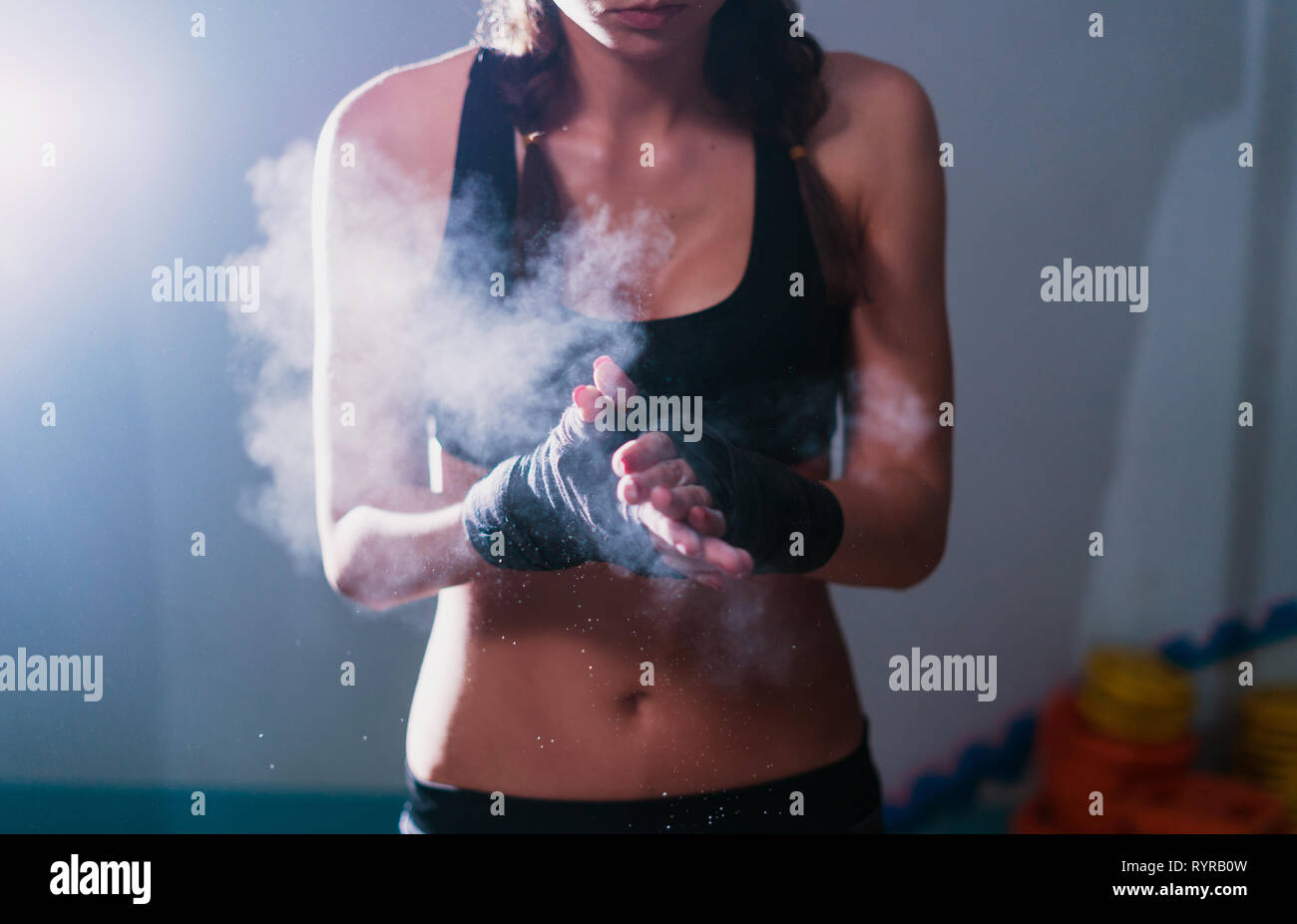 Young fighter boxer girl in training with heavy punching bag Stock Photo
