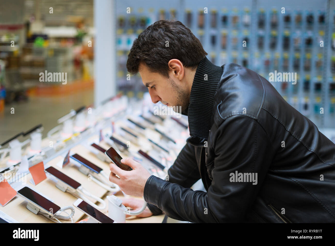 young male customer choosing smartphone in the mobile phone shop Stock Photo