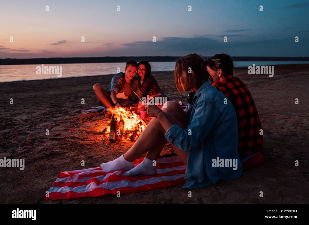 young friends have picnic with bonfire on the beach Stock Photo