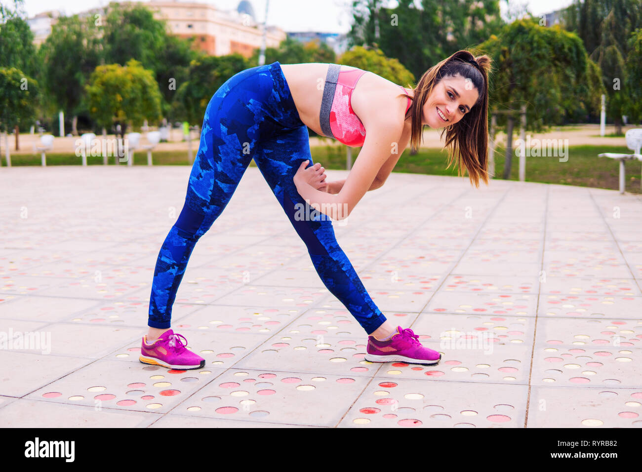 Runner fit woman warming up before sport training in the park Stock Photo