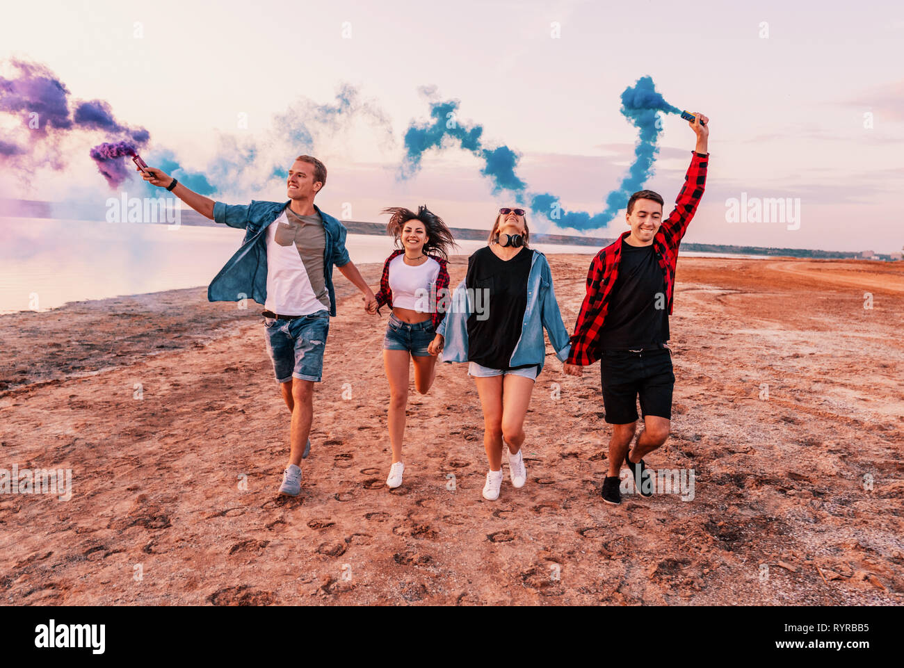 young friends running with hand flare or fusee Stock Photo