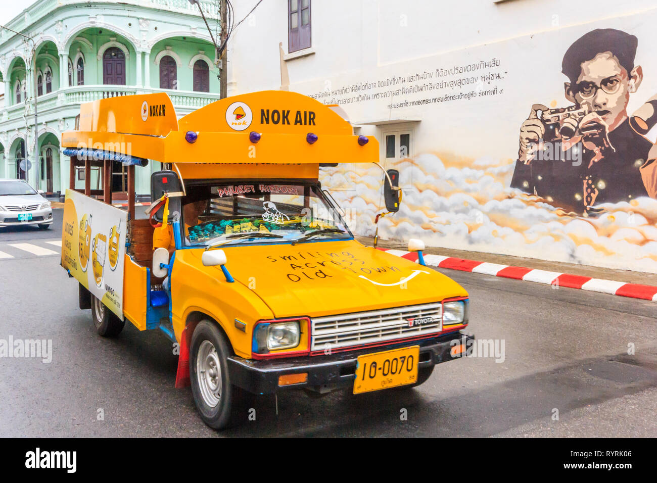 Phuket, Thailand - 11th April 2017: Yellow songthaew or taxi driving past mural of the late King. King Bhumibol was much revered. - Stock Image