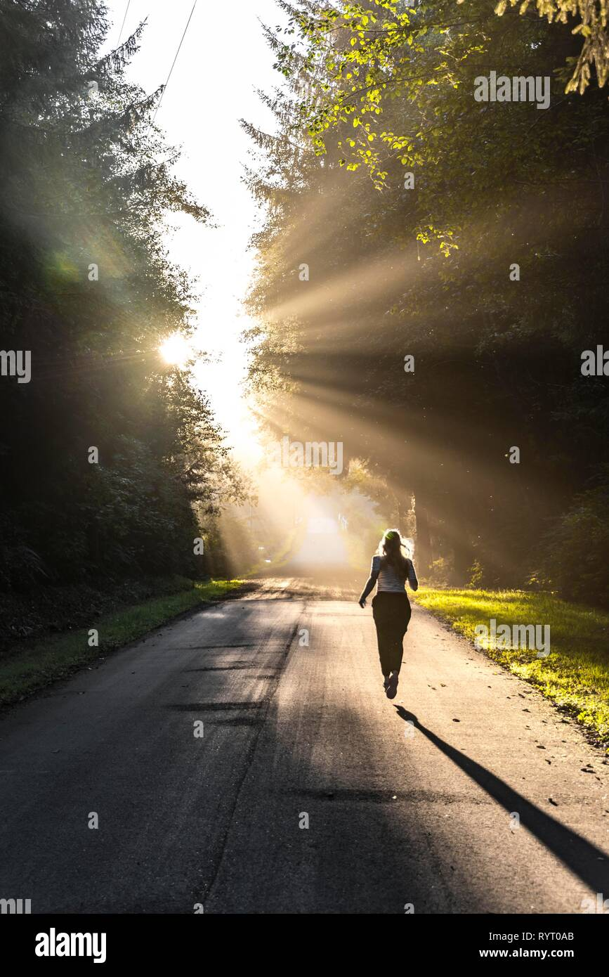 Young woman jogging on a street, sunlight shines through trees, Oregon Coast Highway, Oregon, USA - Stock Image