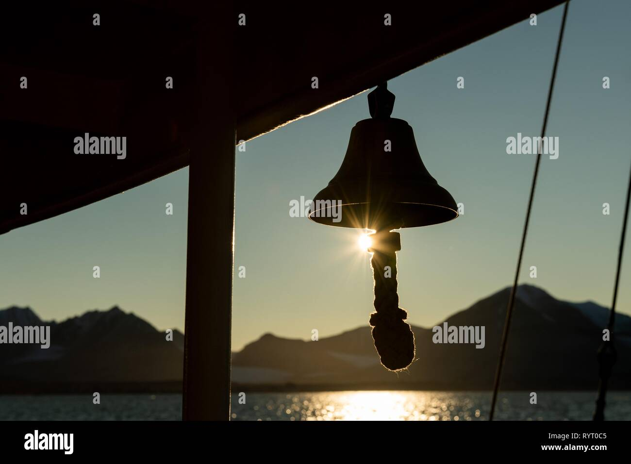 Ship's bell of a sailing ship, Silhouette in front of sun, Spitsbergen, Svalbard, Norway - Stock Image