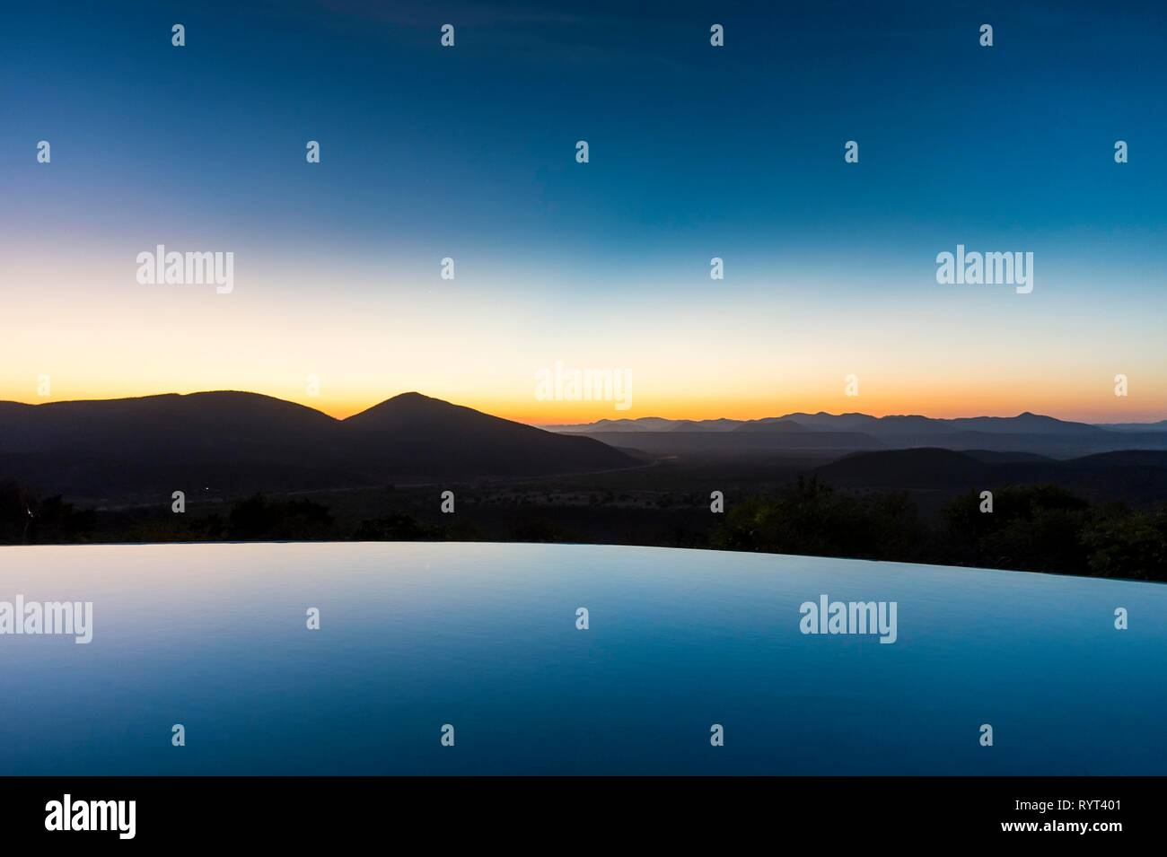 Swimmingpool over beautiful outlook with mountain at sunset, Ovapu, Kaokoland, Namibia - Stock Image