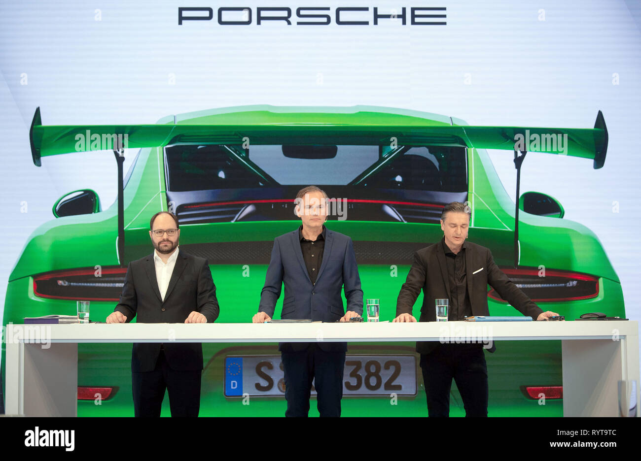 Stuttgart, Germany. 15th Mar, 2019. Josef Arweck (l-r), head of Porsche communications, Oliver Blume, CEO of Porsche AG, and Lutz Meschke, CFO of Porsche AG, are standing in front of a projection during the company's balance sheet press conference. Last year, Porsche was able to sell significantly more of its top models and thus again generate more profit despite rising expenditure. Credit: Marijan Murat/dpa/Alamy Live News - Stock Image