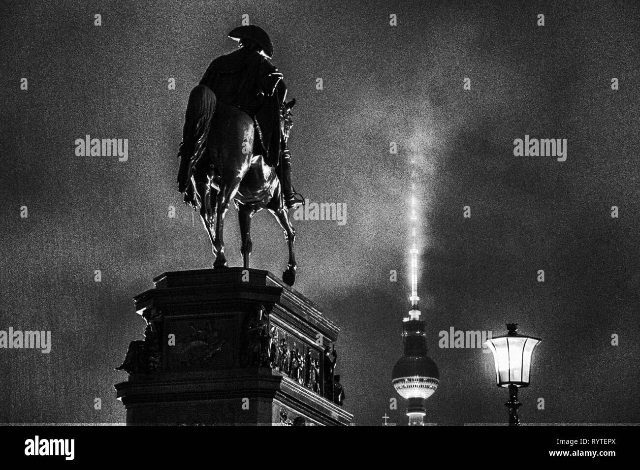 Berlin, Germany. 12th Jan, 2019. A statue of the Prussian king Frederick the Great, popularly called the 'Old Fritz', stands in the drizzle on the magnificent avenue Unter den Linden. In the background is the television tower. Credit: Stefan Jaitner/dpa/Alamy Live News - Stock Image
