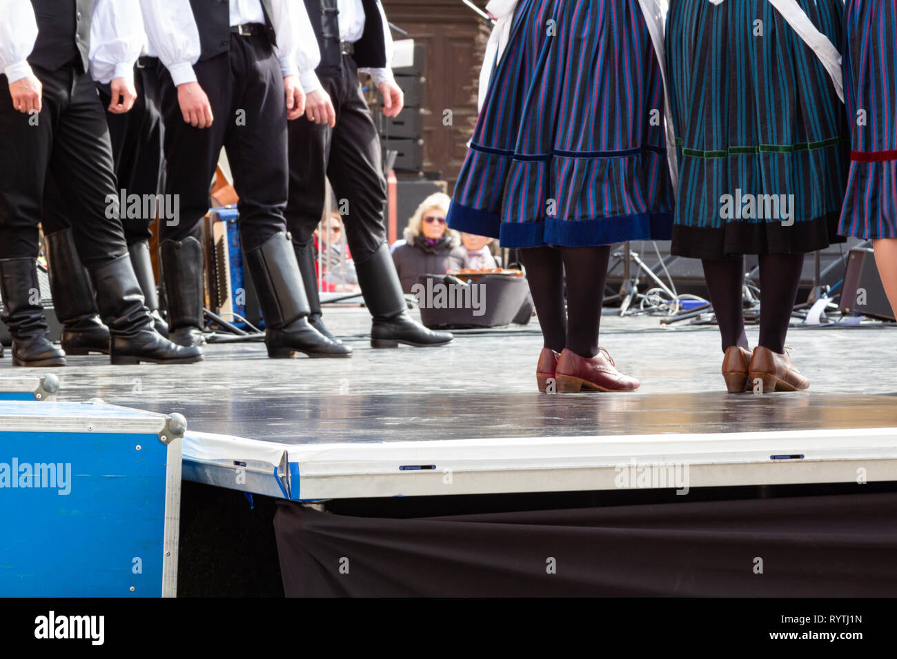 Sopron, Hungary. 15th Mar, 2019. The lower body of male and female folk dancers dressed in traditional costume on stage at Petőfi Square, Sopron, Hungary. Credit: Wahavi/Alamy Live News - Stock Image