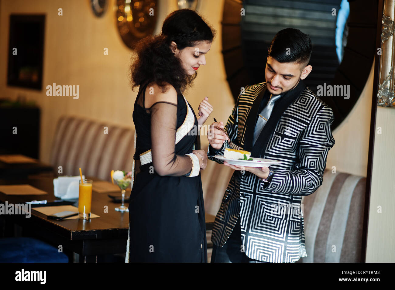 Lovely Indian Couple In Love Wear At Saree And Elegant Suit Posed On Restaurant Hold Plate With Cake Stock Photo Alamy