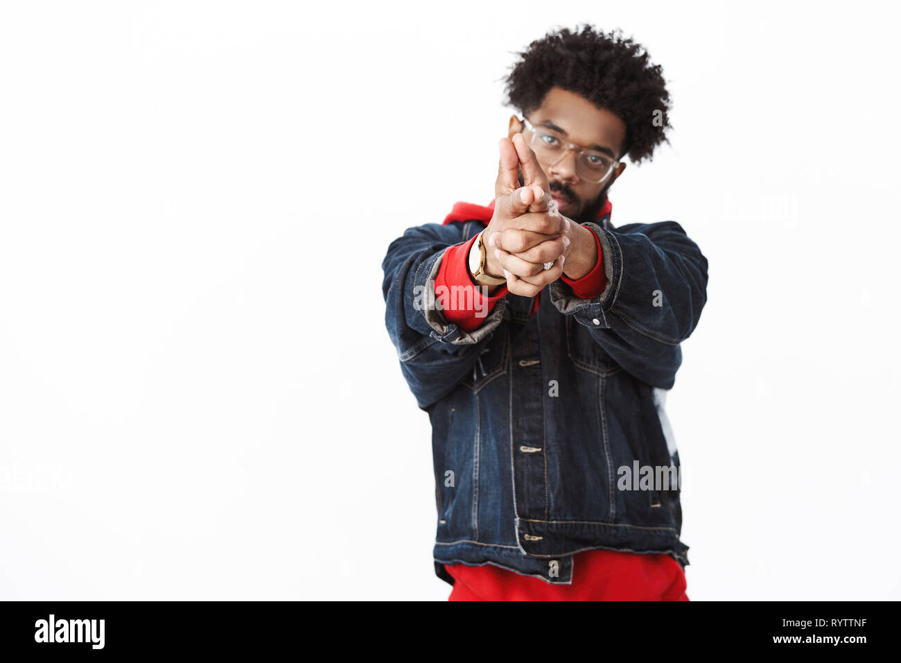 Bang you shot me. Portrait of cool and stylish confident african american handsome guy with beard and afro hairstyle making finger gun with pulled - Stock Image