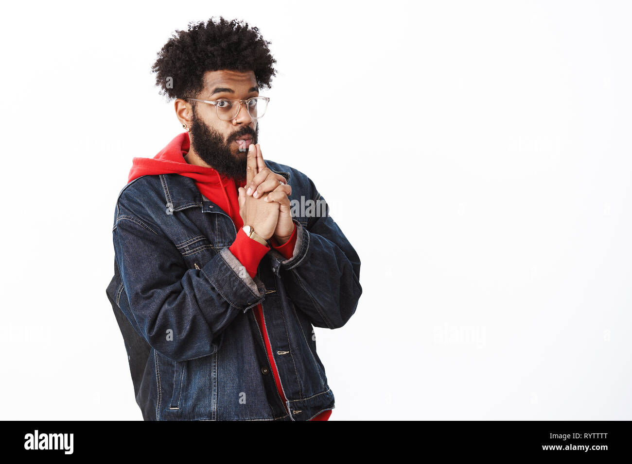 Stylish african-american bearded guy in transparent glasses blowing at gun, making pistol with hands, folding lips and holding hands near mouth as if - Stock Image