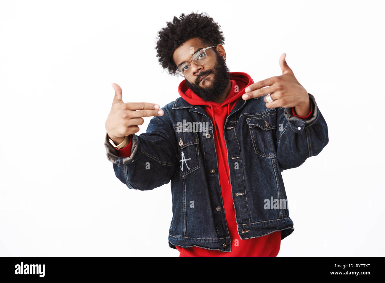 Cool and stlyish handsome african-american young male rapper with beard and piercing showing finger gun gestures pointing at himself, licking lip and - Stock Image