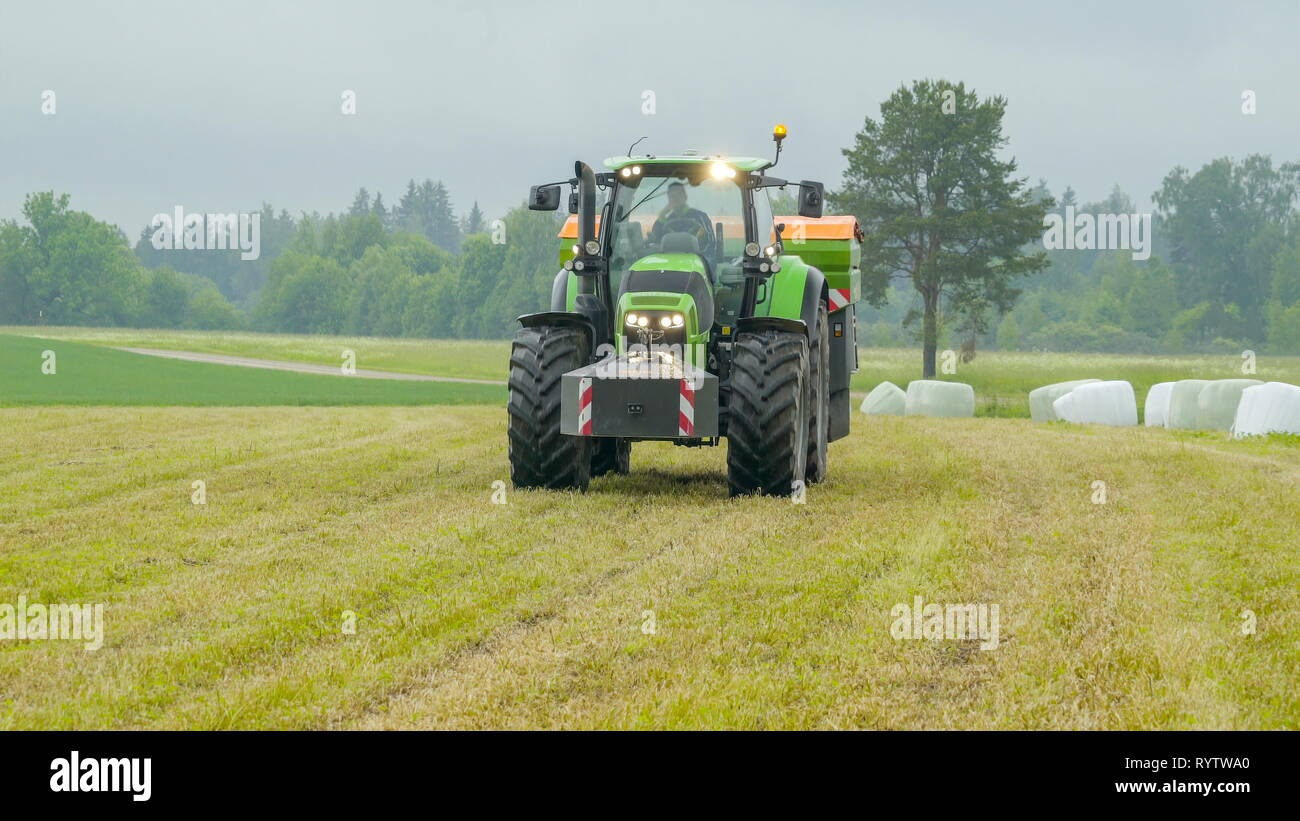 The agriliming truck running on the field it has big wheels with the hays on the side - Stock Image