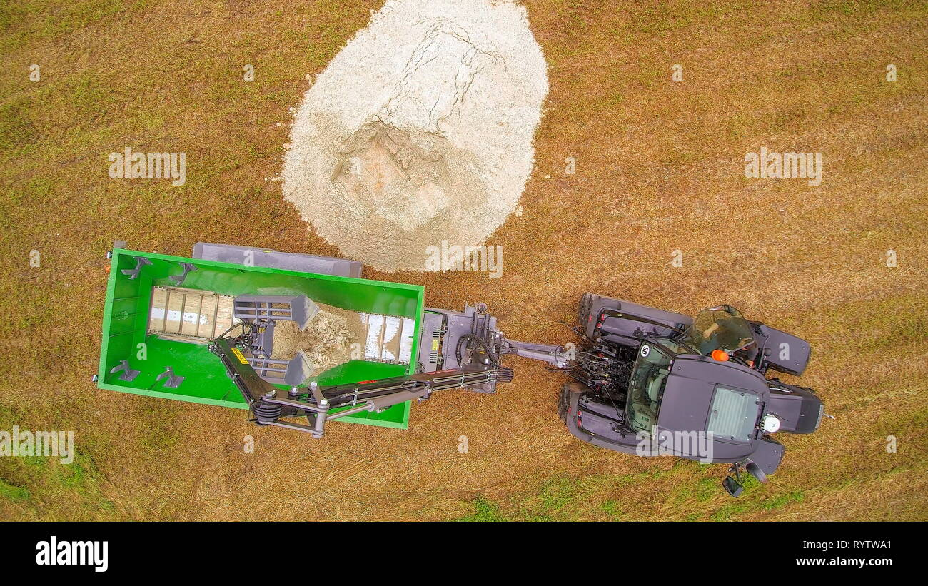 Aerial view of the agriliming activity getting limes on the ground putting to the truck - Stock Image