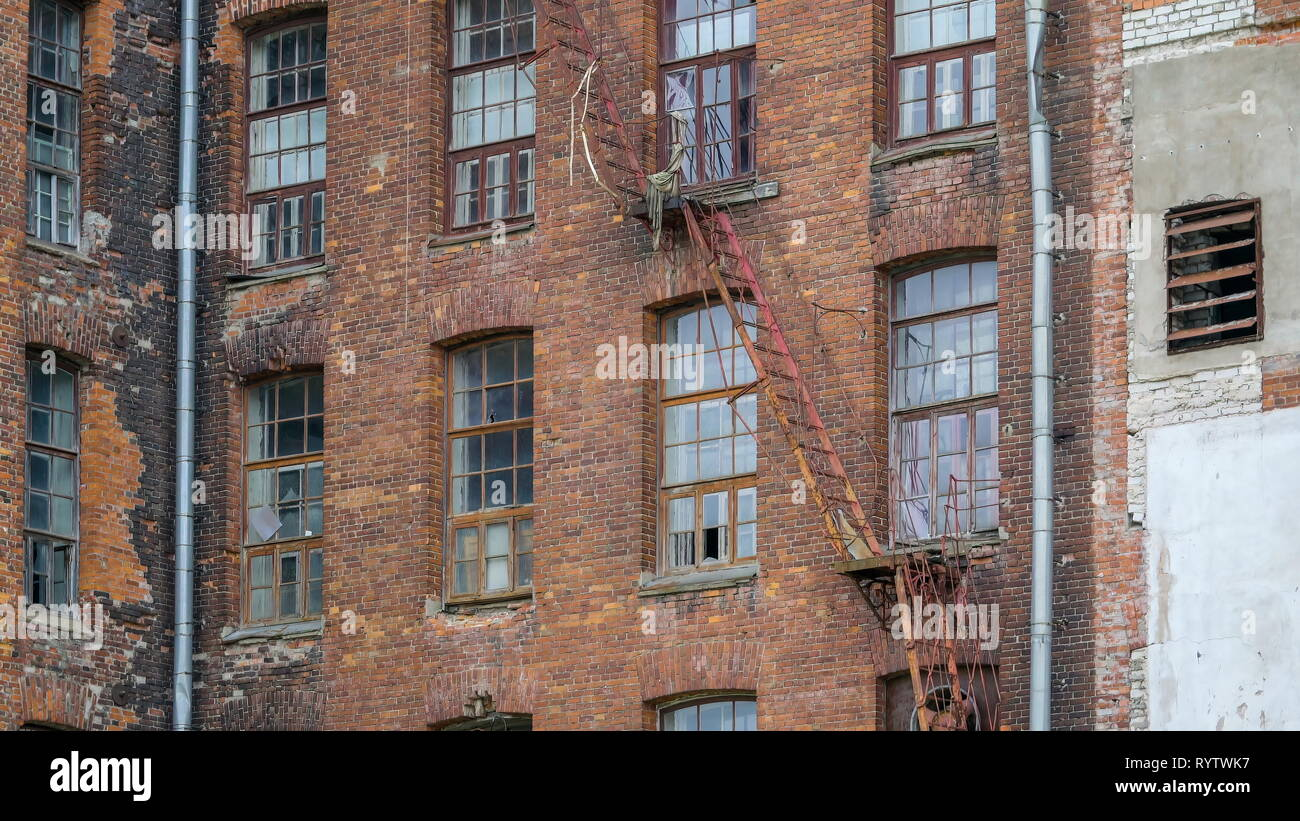 The old windows and ladders of the building on an old textile factory in Kreenholm Stock Photo