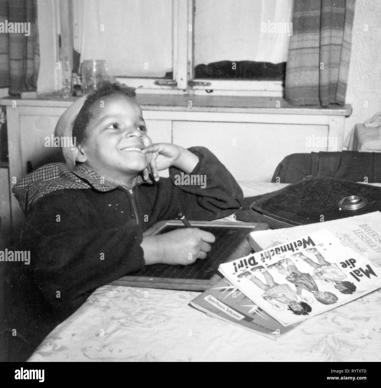 Christmas, handicrafts / painting, black girl painting Christmas images at table, Munich, 1950s, Additional-Rights-Clearance-Info-Not-Available - Stock Image