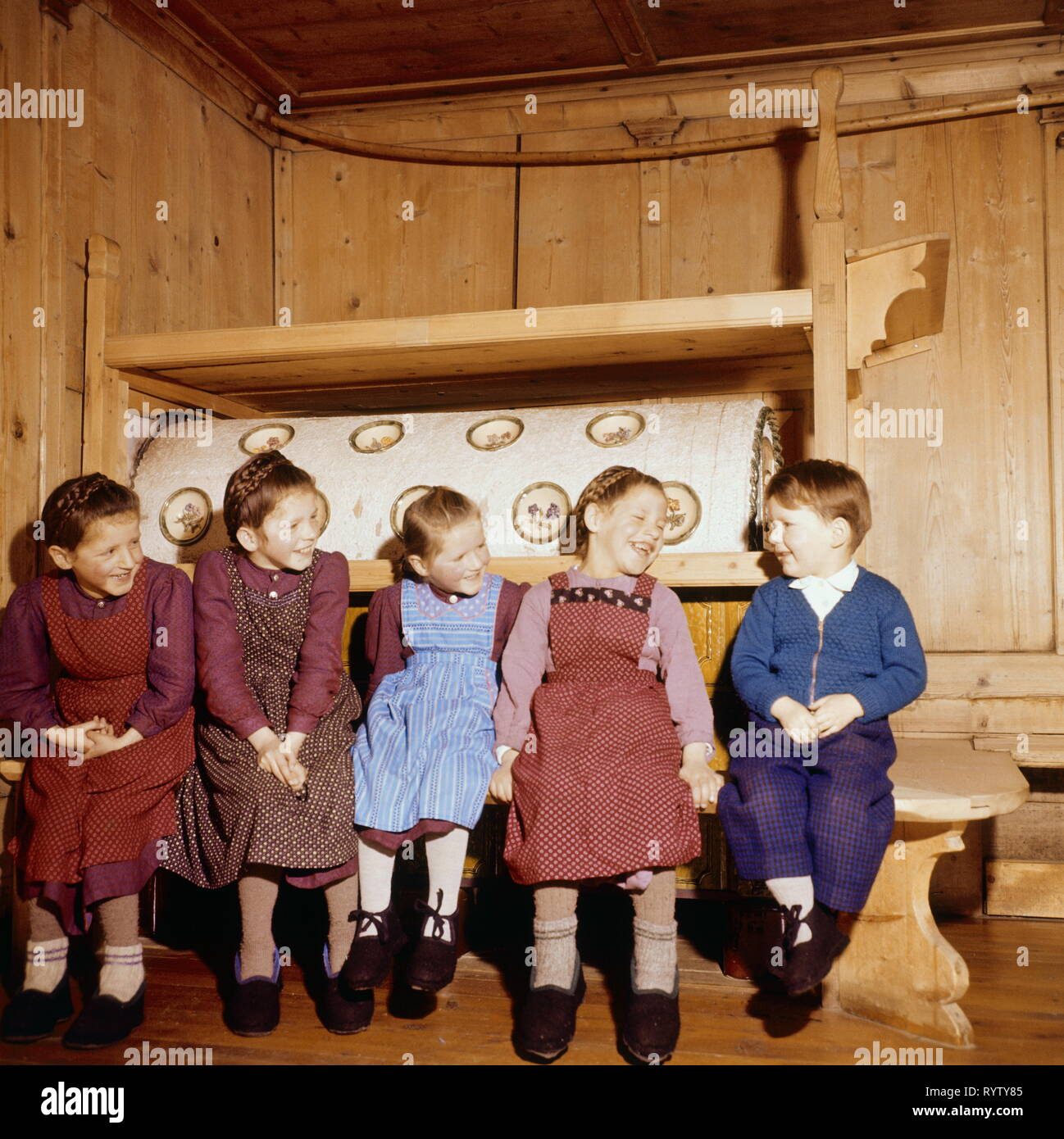 people, children, 1950s, five children sitting at the tiled stove, mountain farmer, Additional-Rights-Clearance-Info-Not-Available - Stock Image