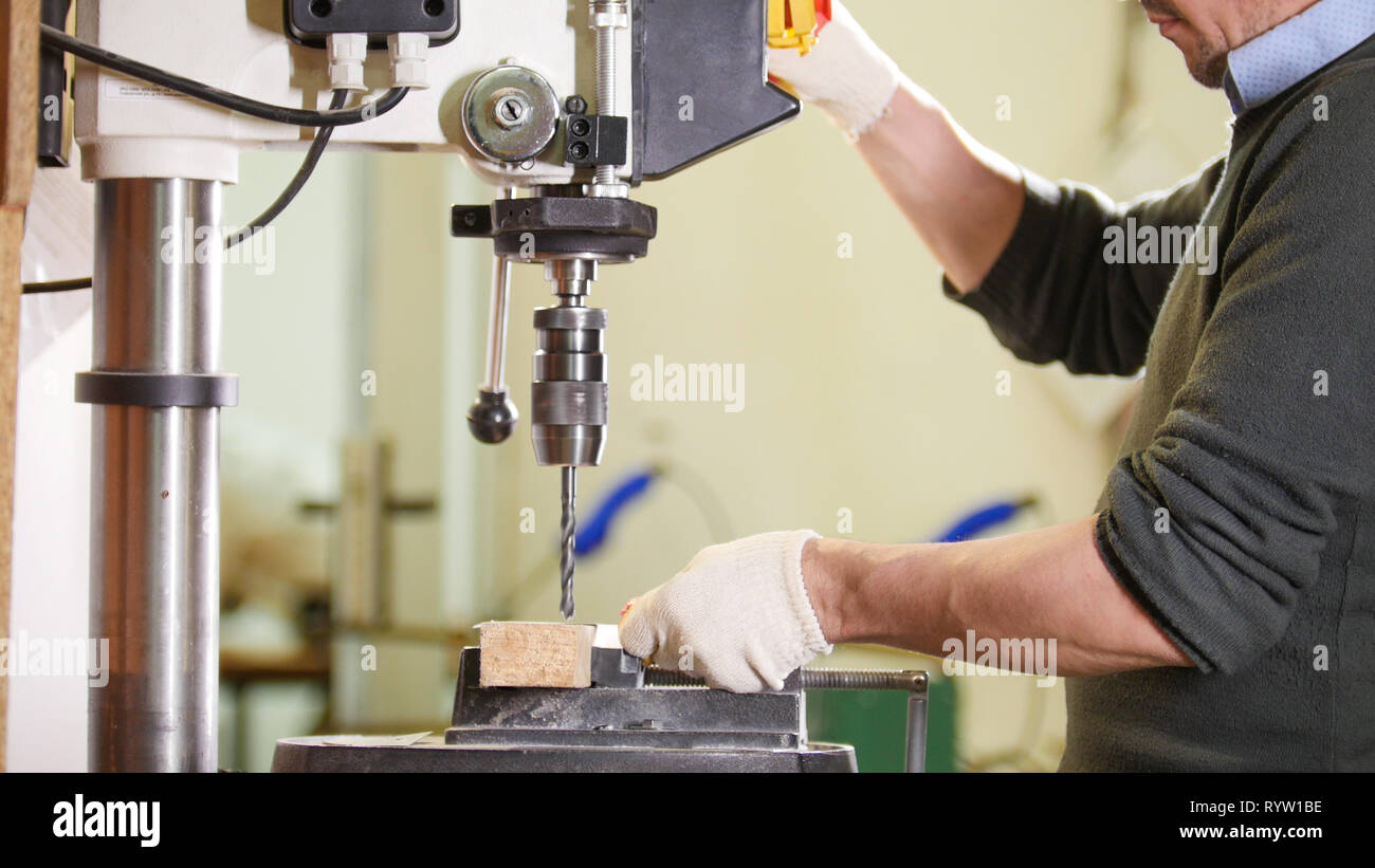 Industrial drilling machine - worker makes holes in metal Stock Photo