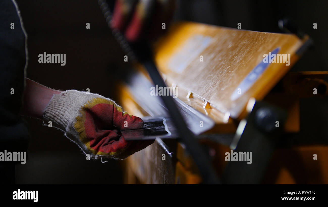 Industrial concept. A worker puts the detail under pressure - Stock Image