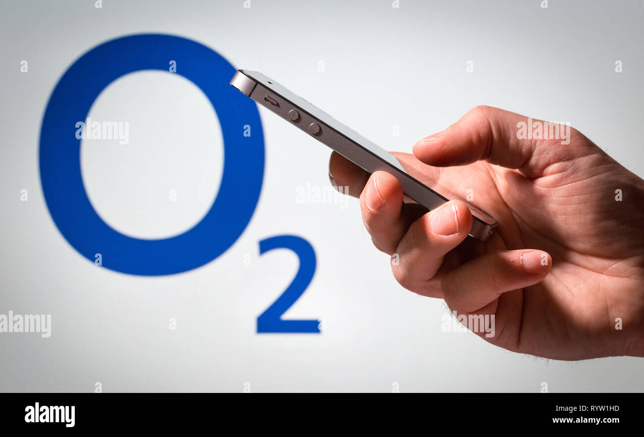 A man using a mobile phone in front of an O2 sign Stock Photo