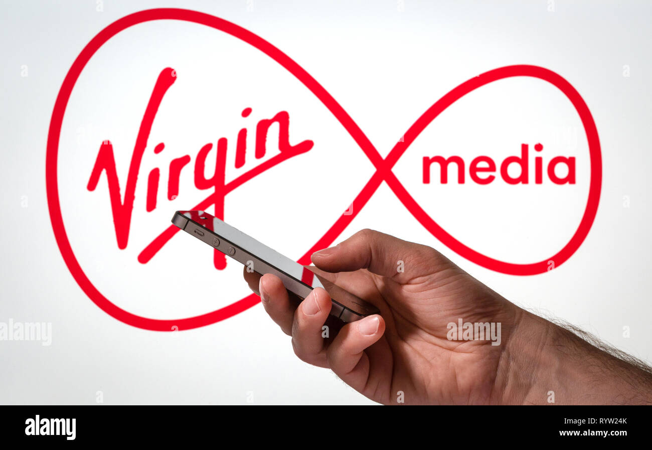 A man using a mobile phone in front of a Virgin Media logo - Stock Image
