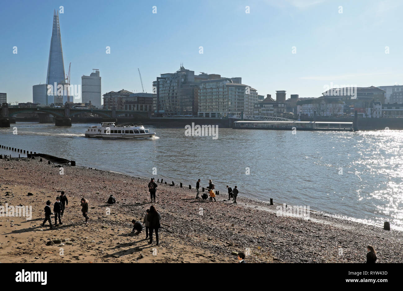 View of boat on River Thames at low tide tourist riverboat, Shard building & schoolchildren mudlarking on shore in London EC4 England UK  KATHY DEWITT Stock Photo