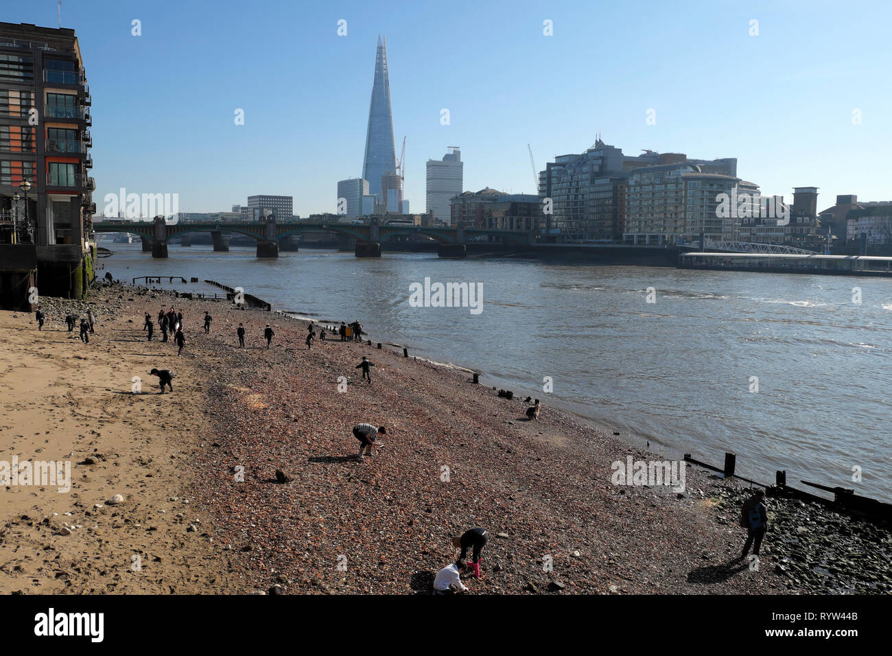View of River Thames at low tide, Shard building, people mudlarking near Queenhithe and Southwark Bridge in London EC4 England UK  KATHY DEWITT Stock Photo