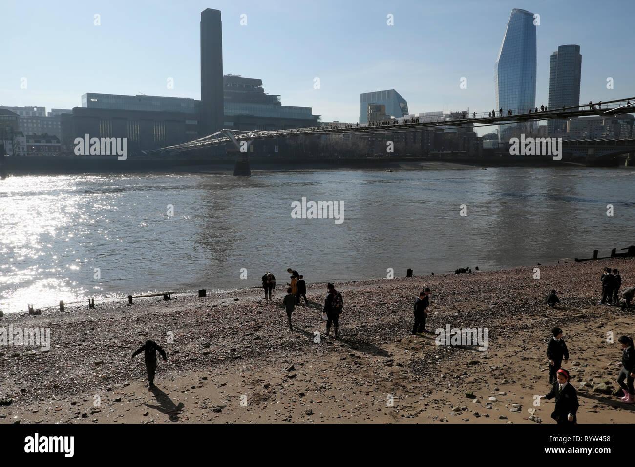 View of River Thames at low tide Tate Modern Art Gallery building & British primary schoolchildren mudlarking London UK Great Britain  KATHY DEWITT - Stock Image