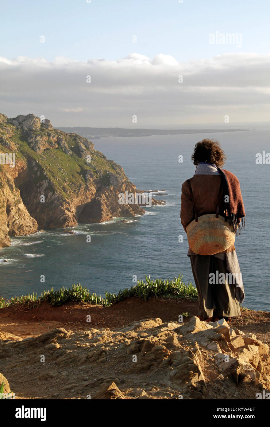 Woman standing at the cliffs looking at the horizon - Stock Image